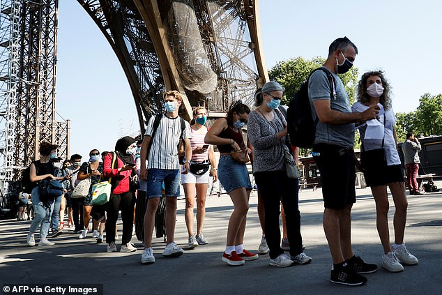 30202602-8472749-Visitors_wearing_protective_facemasks_queue_as_they_wait_for_the-a-6_1593475837139.jpg